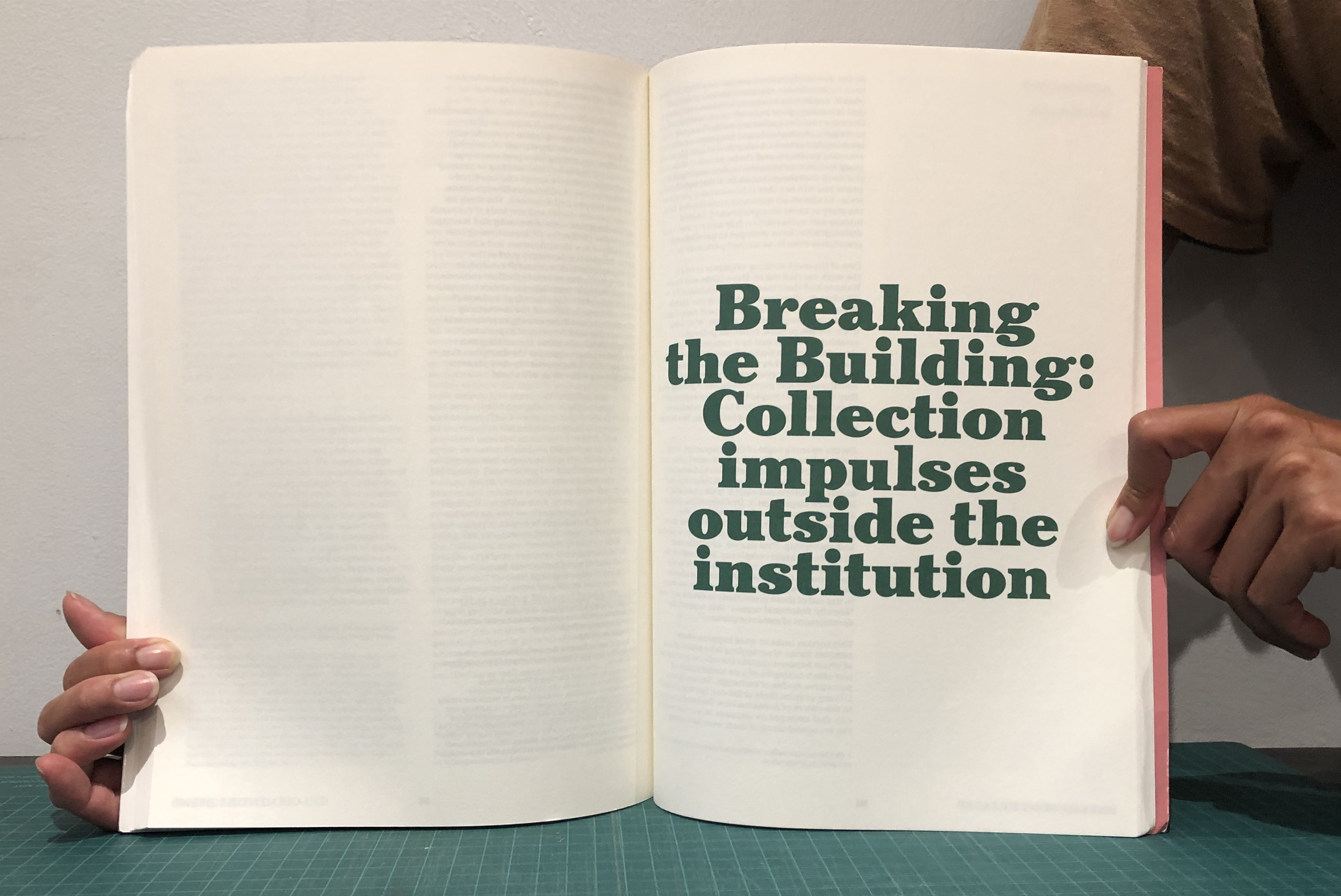 """A book being held open to reveal a spread that reads """"Breaking the Building: Collection impulses outside the institution"""" in green writing."""